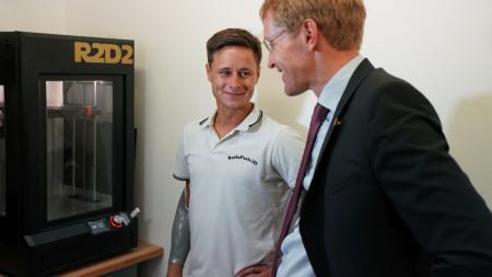 Zwei Männer stehen vor einem 3D-Drucker.
