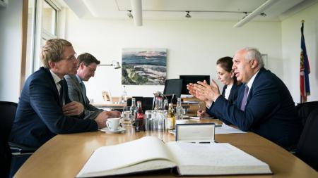 Drei Männer und eine Frau sitzen an einem Tisch. Zwei Männer unterhalten sich.