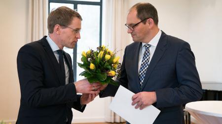 Ministerpräsident Daniel Günther (l.) überreicht Professor Dr. Christoph Brüning einen Blumenstrauß.