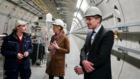 Ministerpräsident Günther und Wissenschaftsministerin Prien besichtigen den hellerleuchteten Tunnel der Röntgenlaseranlage.