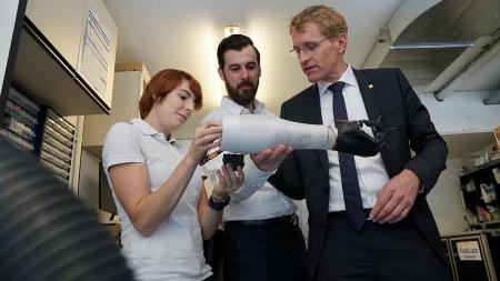 Ministerpräsident Günther (r.) bewundert die Nachbildung eines Arms aus dem 3D-Drucker.