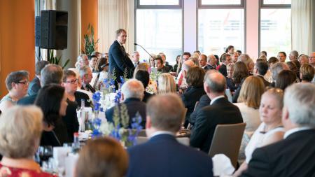 Ein Mann steht in einem Raum voller gefüllter Tische und hält eine Rede.