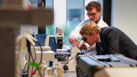 Zwei Männer stehen vor einem Mikroskop.