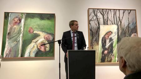 Ein Mann steht an einem Rednerpult. Hinter ihm hängen Gemälde an einer Wand.