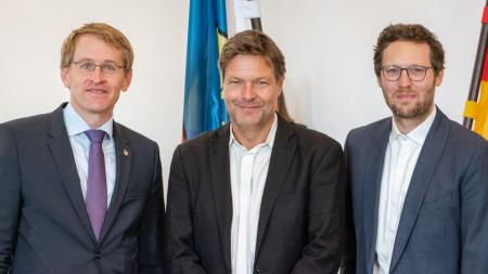 Drei Männer stehen nebeneinander und lächeln in die Kamera