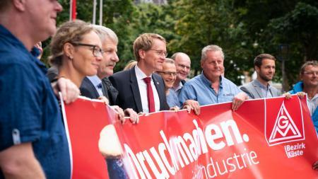 Eine Reihe von Menschen hält gemeinsam ein Plakat hoch.