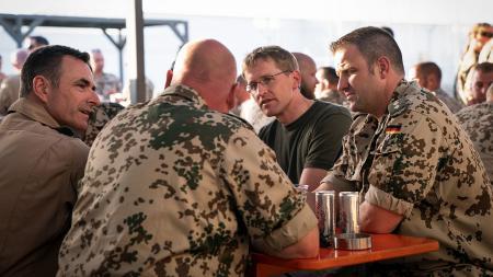 Drei uniformierte Soldaten unterhalten sich mit einem Mann im T-Shirt.