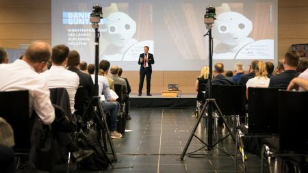Ein Mann steht auf einer Bühne, vor der rechts und links Stuhlreihen aufgebaut sind. Im Gang zwischen beiden Gruppen sind Kameras aufgebaut.