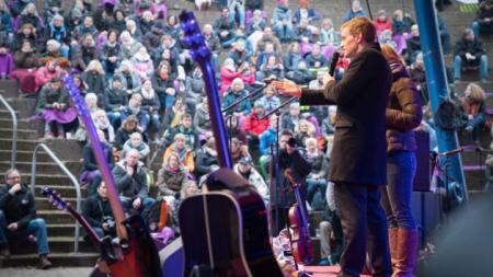 Zwei Personen stehen auf einer Bühne, neben ihnen Gitarren und andere Musikinstrumente. Sie schauen gemeinsam auf eine große Menschenmenge vor der Bühne.