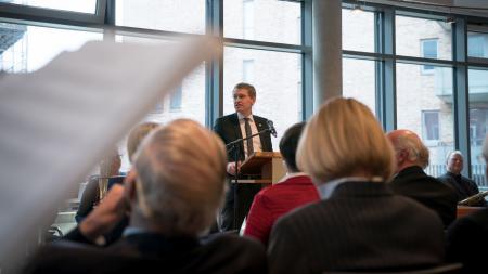 Ein Mann spricht vor mehreren Menschen in einem Raum.