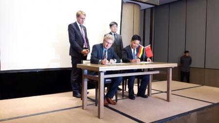 Zwei Männer sitzen an einem Tisch und unterzeichnen ein Blatt Papier. Zwei weitere Männer schauen interessiert zu.