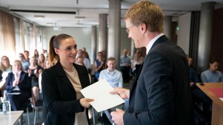 Ein Mann überreicht einer Frau eine Urkunde. Im Hintergrund sind weitere Personen zu sehen.
