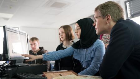 Eine junge Frau mit Kopftuch deutet auf einen Computermonitor. Neben ihr sitzt ein Mann und schaut auf den Bildschirm.