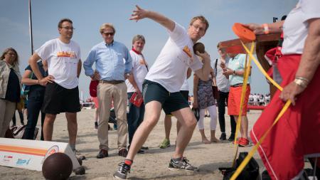 Ein Mann in Sportkleidung stößt eine Kugel. Um ihn herum stehen Menschen, die ihm dabei zusehen.