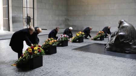 Sechs Menschen knieen vor sechs Gedenkkränzen in einer Halle.