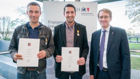 Drei Männer stehen nebeneinander. Zwei von ihnen halten Urkunden in der Hand.