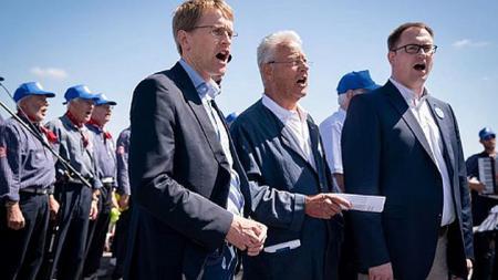 Drei Männer mit Notenblättern in der Hand stehen vor vielen Menschen in Marinekleidung und singen gemeinsam.