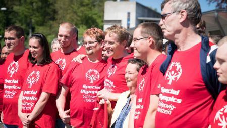"""Menschengruppe mit einheitlichen T-Shirts mit der Aufschrift """"Special Olympics Schleswig-Holstein""""."""