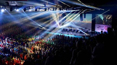 Eine dunkle Halle, die von zahlreichen Scheinwerfern durchflutet wird. Auf einer Bühne tanzt eine Gruppe Jugendlicher. Vor der Bühne stehen viele bunt gekleidete Menschen.