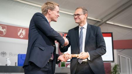 Zwei Männer schütteln einander die Hand und halten einen Holzstab in der Hand.