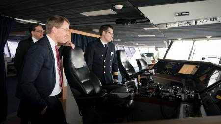 Drei Männer stehen auf der Brücke eines Schiffes.