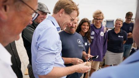 Ein Mann hält eine Muschel in der Hand. Ein anderer Mann hält ein Smartphone daneben. Um sie herum stehen viele Menschen und schauen zu.