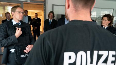 Ein Mann lässt sich von einem Polizisten erklären, wie man eine Schutzweste anlegt.
