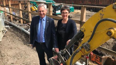 ein Mann und eine Frau stehen auf einer Baustelle neben einem gelben Bagger, von dem nur der Greifarm ein wenig zu sehen ist.
