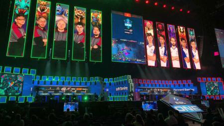 In einer großen Halle sind E-Sportler auf der Leinwand abgebildet, die auf der Bühne gegeneinander antreten.