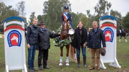 Das Bild zeigt die Siegerin auf ihrem Pferd zwischen vier weiteren Personen.