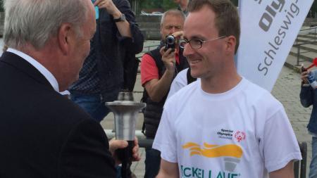 Innenminister Hans-Joachim Grote übergibt die Fackel an den Athleten Sebastian Kröger. Im Hintergrund steht ein Werbebanner für die Spiele.