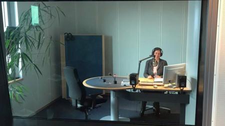 Eine Frau sitzt in einem Sendestudio am Mikrofon