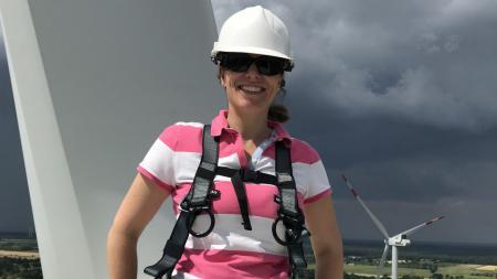 Eine Frau mit einem Helm auf dem Kopf steht auf der obersten Plattform eines Windrads.