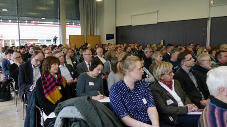 Menschen im Publikum lauschen einem Vortrag