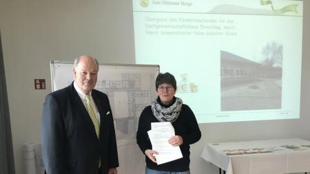 Innenminister Hans-Joachim Grote übergibt einen Förderbescheid über 450.000 Euro an Christiane Ostermeyer, Bürgermeisterin der Gemeinde Owschlag.
