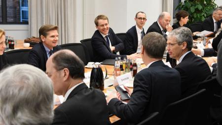 Mehrere Menschen sitzen an einem langen Tisch und sprechen miteinander.