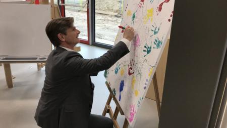 Der Minister signiert das Kunstwerk der Kita-Kinder