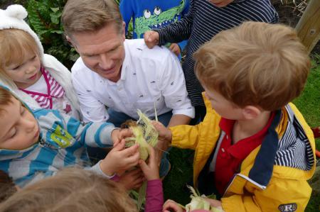 Minister Garg mit Kindern, ein Maiskolben wird inspiziert