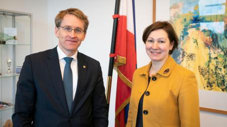 Daniel Günther und die lettische Botschafterin stehen nebeneinander. Im Hintergrund ist die Flagge Schleswig-Holsteins zu sehen.