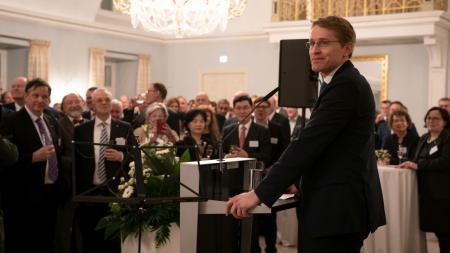 Ein Mann steht an einem Rednerpult und spricht zu vielen Menschen.