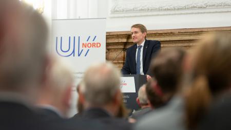 Ein Mann steht am Rednerpult und spricht zu Menschen.