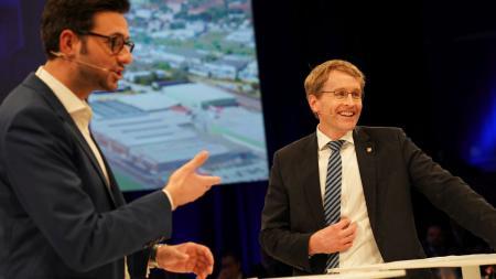 Ministerpräsident Daniel Günther steht gemeinsam mit dem Moderator der Veranstaltung, Christopher Scheffelmeier auf der Bühne.