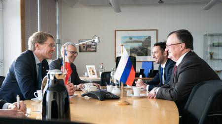Vier Männer sitzen an einem Tisch und unterhalten sich.