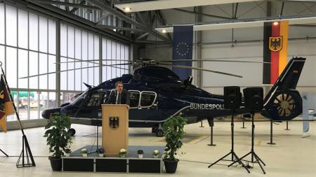 Daniel Günther hält eine Rede. Im Hintergrund ist ein Hubschrauber der Bundespolizei.