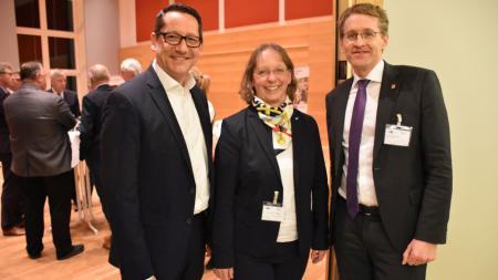 Daniel Günther steht gemeinsam mit zwei Vertretern der IHK im Landtag.