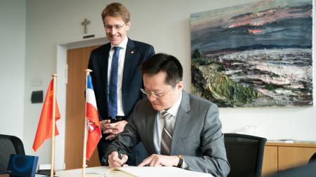 Der chinesische Generalkonsul trägt sich in das Gästebuch Schleswig-Holsteins ein, Daniel Günther steht dahinter.