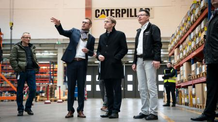Drei Männer stehen in einer Werkshalle. Einer der drei erklärt den anderen etwas.