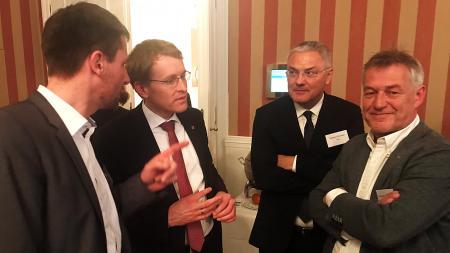 Vier Männer stehen nebeneinander und unterhalten sich.