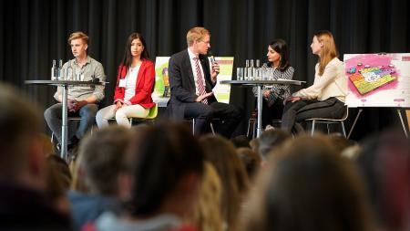 Auf einer Bühne sitzen 5 Menschen und diskutieren miteinander. Vor der Bühne sitzen viele weitere Menschen.