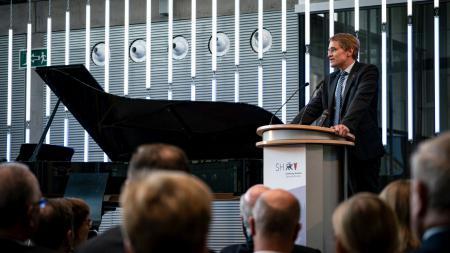 Ministerpräsident Daniel Günther steht am Rednerpult und spricht zu Menschen.
